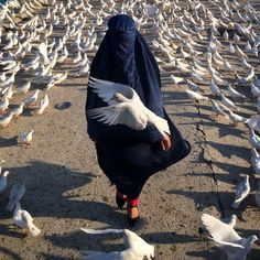 A woman covered by a burqha  passes by the 'Roze Sharif' holy shrine. This place is home to countless white pigeons; the pigeon being the symbol of freedom in Afghanistan