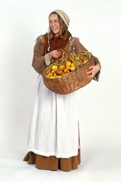 Elizabethan-age peasant woman holding basket of apples, smiling