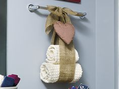 Tie burlap ribbon into a bow around a towel bar, leaving a loop big enough to host rolled up hand and bath towels. I would use beautiful ribbon instead.