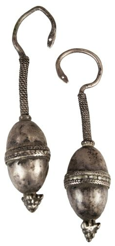 "Silver pair of earrings, with a dangling braided rope and an attached, solid, egg-shaped form with a decorative band around it. Size: 3"" Date: 1300 AD"