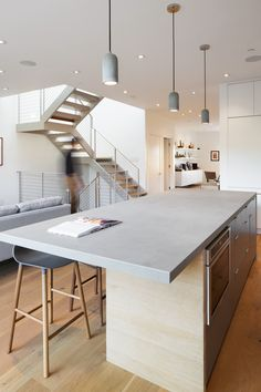 Love this contemporary kitchen. Concrete counter top with overhang for eating