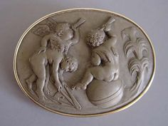 """LAVA carved cameo brooch depicting cherubs using early instruments of astronomy to view the stars, a very unusual piece, 2-1/3"""" by 1-3/4""""."""