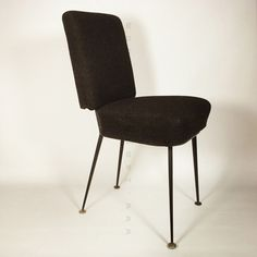Chair covered with a  dark grey / black fabric.