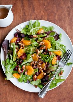 Recipe for simple holiday green salad recipe featuring a mix of baby greens, oranges, dried cranberries and spicy candied walnuts and orange vinaigrette.