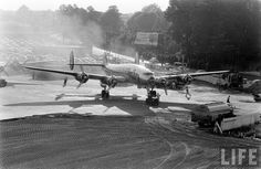 Atlanta Municipal Airport, 1956  The ground crew scurries as all four engines come to life on an Eastern Air Lines Constellation.