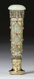 A JEWELLED TWO-COLOR GOLD BOWENITE HANDSEAL BY FABERGÉ, WORKMASTER MICHAEL PERCHIN, ST. PETERSBURG, 1896-1908. Of tapering cylindrical form, the hardstone body set with stylized gold-mounted rose-cut diamond arrows within interlaced waved bands, set with cabochon rubies at intervals, with later gold-mounted matrix. Provenance: Lord and Lady Iveagh.