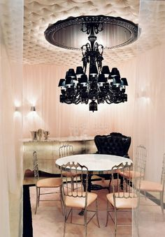 Glamour dining room with a round dining table, metal dining chairs, and an oversized black Philippe Starck lighting piece.