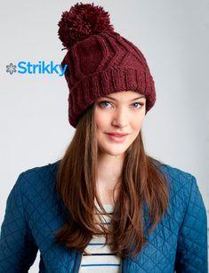 Модная шапочка от Patons с помпоном вяжется из шерстяной пряжи. Узор состоит из жгутов, имеющих вид ломаных прямых линий, несколько ассиметричный.