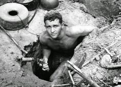 """Sergeant Ronald Payne, 21, of Atlanta, Georgia, emerges from a Viet Cong tunnel holding his silencer-equipped revolver with which he fired at guerrillas fleeing ahead of him underground. Payne and others of the 196th light infantry brigade probed the massive tunnel in Hobo Woods, South Vietnam, on January 21, 1967, and found detailed maps and plans of the enemy. The infantrymen who explored the complex are known as """"Tunnel Rats."""" (AP) ~ Vietnam War"""