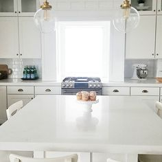 #whitelanedecor @whitelanedecor All white kitchen, brass pendants, brass knobs with white cabinets, cafe series appliances, subway tile with frost gray grout, white marble qaurtz, glass stacked cabinets, white kitchenaid mixer, craftsman modern kitchen, famrhouse modern kitchen, ikea ingolf barstools,