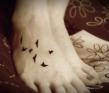 a bird or butterfly for each person? Google Image Result for http://cdnimg.visualizeus.com/thumbs/bd/fc/bird,tattoo,foot-bdfcb9f104b29c6f607e0edb6a0d6747_m.jpg
