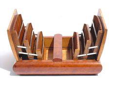 Portasigarette da tavolo. È una scatola di gusto art déco, fatta di legno e rivestita con due diversi piallacci di radica. Ha un paio di coperchi che, aprendosi, scoprono sei scomparti della capienza complessiva di 78 sigarette. Dimensioni: 6 cm. di altezza a coperchi chiusi (che diventano 15 cm. a coperchi aperti), 26 cm. di larghezza e 21 cm. di profondità. #vintage