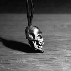Side view of the hand made Hex Cavelli Skull Core Pendant. Solid Silver Skull knife bead pendant on Leather Thong