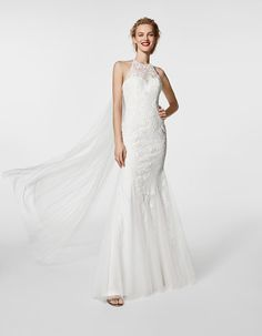A soft tulle and lace gown with kick flares at the bottom. The back is open but the neckline ties up with a floor length bow almost creating a train. Also available in black lace with a nude underlay.