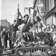 Children celebrate the surrender of the remaining German forces in the Netherlands with their Canadian liberators, May 51945