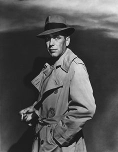 """Humphrey Bogart in his portrayal of Rick Blaine in the film """"Casablanca,"""" wearing his iconic trench coat and Fedora."""