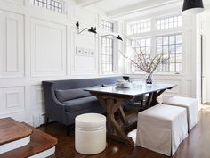 Charming dining room features bright white walls accented with decorative molding holding two black swing arm sconces above a gray wingback dining sofa facing a zinc top trestle dining table also seating two light gray skirted dining stools and a round white nailhead stool.