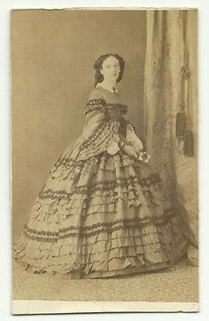 1860's Lady with flowers in a very nice day dress with lots of ruffles, pagoda sleeves, lacy under sleeves and pretty coiffure, CDV.