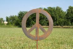 "Metal Peace Sign Garden Stake. Rusted peace sign garden stake is perfect for your landscape or small enough to stick into a flower pot! Stake is roughly 20"" tall. The peace symbol is cut from thick steel, so this stake is light-weight but sturdy. This rusted stake will add the perfect charm to your landscape or garden -- makes a great gift! We hope you'll love our garden art as much as we love making it! All of our products are made by the two of us, in our own shop. 100% made in USA and..."