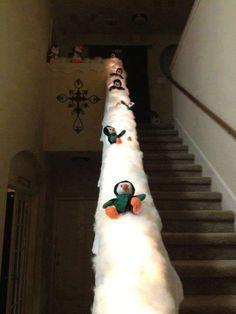Here are some fun ways to decorate your stairs this Christmas! Grinch Stole Christmas Stairs (source unknown) Candy Cane Stair Rails Christmas Photo Railing–Hang up your photos on the stairs with ribbon…or even Christmas cards! Sliding Penguin Railing (via Pinterest) Put Frosty's hat on the end of the stairs…adorable! (source unknown) Hanging Ornaments – Made …