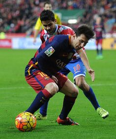Lionel Messi of FC Barcelona is challenged by Nacho Cases of Sporting Gijon during the La Liga match between Sporting Gijon and FC Barcelona at Estadio El Molinon on February 17, 2016 in Gijon