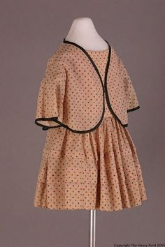 1850-1860  Tan wool dress and jacket printed with brown, green, blue and red pinwheels. Round neck. Short puffed sleeves and jacket trimmed in black velvet ribbon. Center-back closure with round black buttons. Pleated skirt with two horizontal tucks. Bodice lined; skirt unlined; jacket unlined. Nearly all hand-stitched; much fine back-stitching; seams finished by hand.
