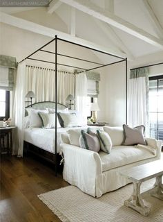 A bright and airy bedroom with vaulted ceilings and a simple canopy bed echoes the tranquil, open feeling of its location on Florida's Gulf Coast  (via Chris Lewis)