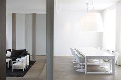 Living area with a black reception area / living room and a white dining table | Espace à vivre avec un salle de réception / salon noir et une salle à manger blanche