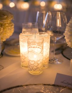 Brilliant & easy DIY centerpiece for wedding decor: add white lace around glass candleholders. I'm sure you can get those glass votive holders for CHEAP + here are the LED tea light candles to recreate the look: http://www.flashingblinkylights.com/light-up-products/flickering-led-candles.html