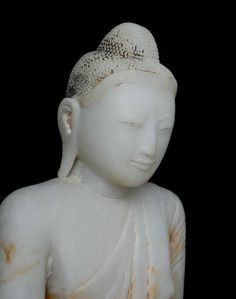 19th Century, Marble Mandalay Buddha: At the end of the 18th Century a new style of Buddha images emerged in Burma. Centered around the city of Mandalay which was considered the heart of Burma's Buddhist art, thanks to the patronage of King Mandon, a devout Buddhist himself. Mandalay Period art focused on a realism in the features of the Buddha and his attire. The style of the faces is oval with long, pointed noses, full lips and almond eyes defined by clear eyebrows.  Elongated to the should...