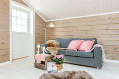 Loftsstua på hytta kan brukes til å slappe av, se på tv eller lese bok. Her har vi brukt en kald og knall rosafarge på puter og duk for å gi en frisk kontrast til den varme fargen på panelet. Couch, Furniture, Home Decor, Settee, Decoration Home, Sofa, Room Decor, Home Furnishings, Sofas