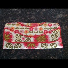 """Vera Bradley wallet Vera Bradley wallet in red, pink, olive green, yellow on crime background.  It measures 10"""" by 5"""". It has a large interior zip compartment,  open fold compartment credit card slots, and a snap closure.  It has a small circle on left side which might have at one time a strap but now there is no strap. Excellent condition. Vera Bradley Bags Wallets"""