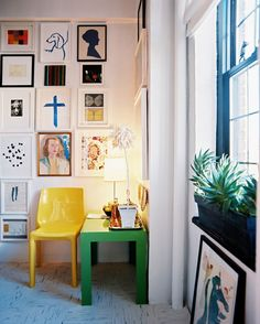 Eclectic - A green Parsons table and a yellow molded-plastic chair below a gallery wall of art