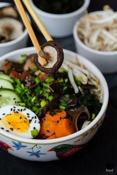 Ramen to popularna japońska zupa na bazie wywaru z warzyw, glonów, grzybów oraz mięsa. Przepis na mój ramen jest wegański, nie licząc tego, że podałem go z jajkiem. Przepis na wywar z pastą miso krok po kroku wraz z proponowanymi dodatkami: marynowanym wędzonym tofu, grzybami mun i shiitake, kiełkami fasoli mung, glonami watakame, ogórkiem, szczypiorkiem i czarnym sezamem.