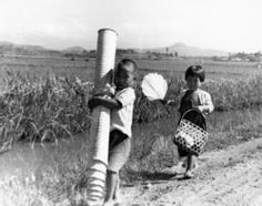 Korean War refugees photographed by Frank Winslow included children carrying household belongings. (Bellingham, WA)