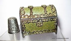 Green leather, with gilt mounts on this casket shaped thimble case.Hinged lids opens to reveal velvet thimble recess with metal thimble. English cir 1880.