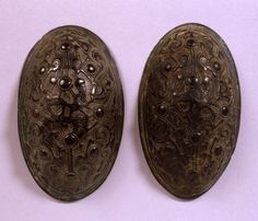Brooch; bronze; oval; 10 low round bosses; interlace Gripping-Beast design; plain border.
