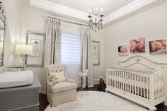 French nursery features a baby photos over a white French crib dressed in pink bedding facing a light beige tufted wingback glider and glass and nickel accent table placed in front of windows dressed in ivory and silver drapes layered over sheer panels.