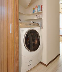 階段下に洗濯機がぴったり収まるスペースをつくりました。造り付けで棚も備えています。