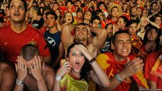 Spanish fans react while watching on a giant outdoor screen on Paseo de La Castellana street in Madrid during the UEFA Euro 2012 semi-final match against Portugal.