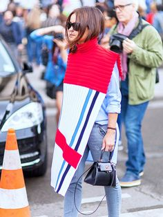 Miroslava Duma wearing a crisp button-up with jeans, and a colorful poncho
