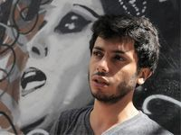 """Yazan Halwani, in front of one of his street painting of Fayruz. One of the youngest graffiti artists in the Middle East and probably one of the most talented Lebanese street art painters emerging today. Beirut became his playground, and Niels Shoe Meulman – an artist from Netherlands – his mentor. When Halwani discovered what Meulman defined as """"Calligraffiti"""".  He copied a calligraphy book from his uncle and taught himself the ancestral techniques."""