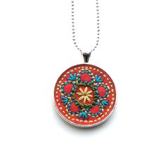 Flower vintage inspired hand embroidered pendant, Tangerine with Blue and Greens. $18.00, via Etsy.