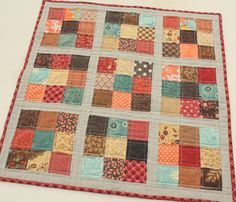 "After putting away the Halloween decorations, my kitchen table was looking really bare.  I decided I ""needed"" a new fall-ish mini quilt to spice up my bare space.  I've also been inspired by all the mini-quilts growing out there in quilt-cyberspace, thanks to Amylouwho.  I was lucky enough to get one of those Moda mini (2.5″) charm packsin the new collection, Late Bloomers by Sandy Gervais in my Sewing Summit swag bag.  Perfect. I added a few prints from the stash – I wanted a little more…"