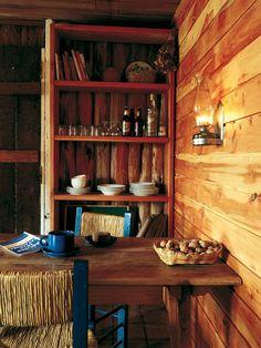 Living comedor de una acogedora casa patagónica con paredes recubiertas en madera, muebles estilo campo y espacio de almacenamiento a la vista.