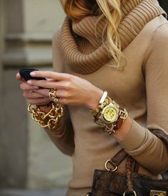 lots of chunky gold layered jewelry (and love the tan cozy cowl neck sweater)