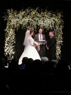 Floral arch with white up lights against black backdrop