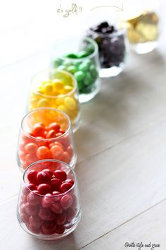 Easy and fun candy display idea for St. Patrick's Day: A rainbow of skittles vases with gold coins at the end.