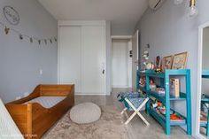 Quarto infantil com cama baixa e estante na cor azul turquesa.