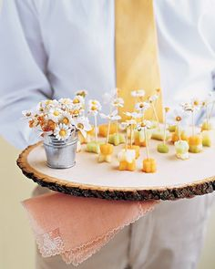 Set the stage for a sunny celebration with these mini bites. Glue paper flowers to the top of toothpicks for an easy-to-grab snack. Add a mini bucket or a small cup for used skewers.